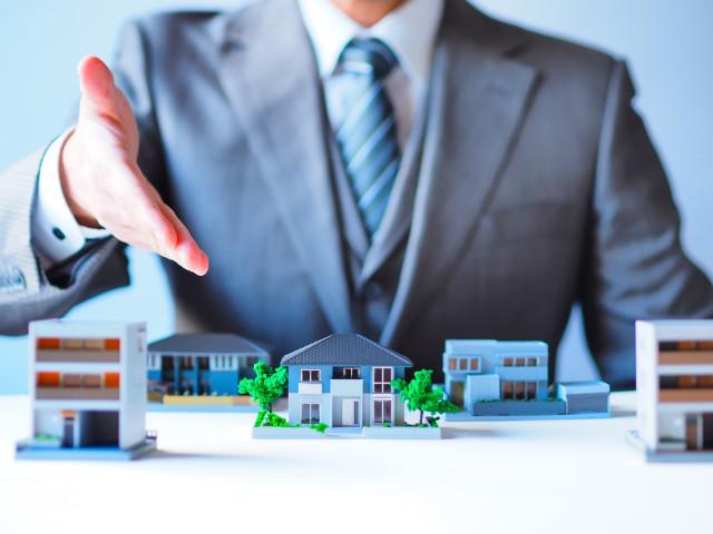 家の模型と不動産業者